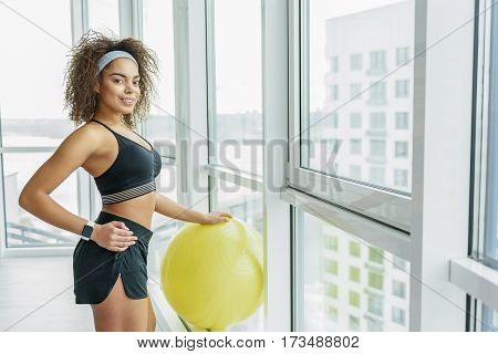 Cheerful girl is standing near window and putting hand on big yellow ball. She looking at camera with smile
