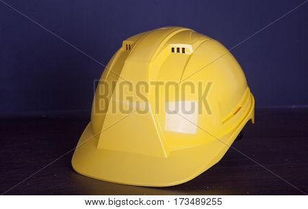 Yellow safety helmet on dark blue background