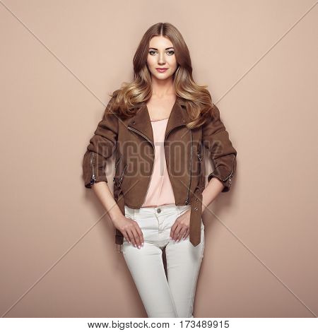 Young blond woman in brown jacket and white jeans. Girl posing on a beige background. Jewelry and hairstyle. Fashion photo