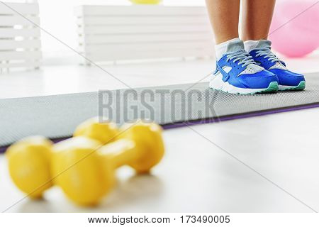Slim trotters dressed in comfortable blue sneakers. Girl is standing on mat for fitness. Close-up