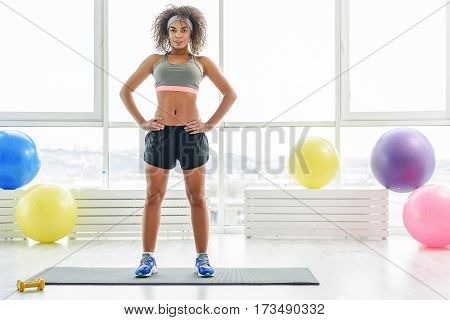 Smiling girl is standing at mat for fitness. She putting hands on waist and looking at camera