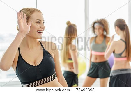 Hilarious laughing girl is standing in light gym. She greeting someone and looking aside