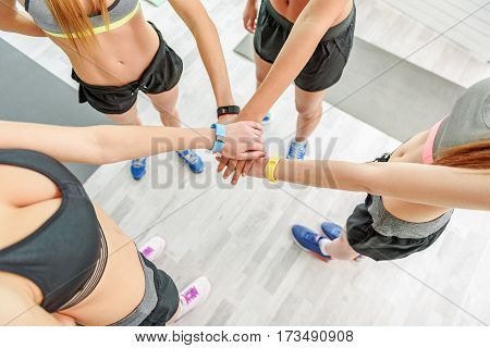Slim women are standing in circle. They strengthening their team spirit. Top view