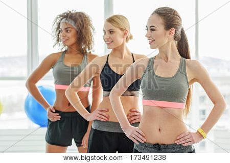 Hilarious young sportive women are doing exercise. They putting hands on waist and turning heads aside