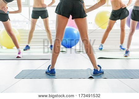 Young women with athletic figures and slender legs doing exercise on mats