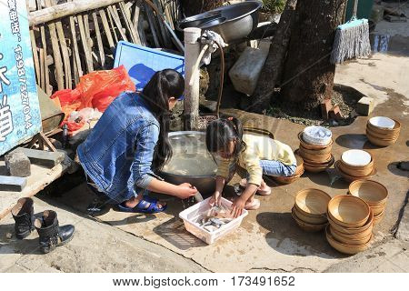 Yuanyang, China - February 20, 2017: Hani Woman And Her Daughter Busy In Their Daily Activities. Han