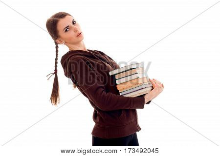 Teen girl with pigtails holds many books isolated on white background