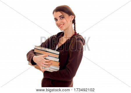 smiling teenage girl stands sideways and keeps books isolated on white background