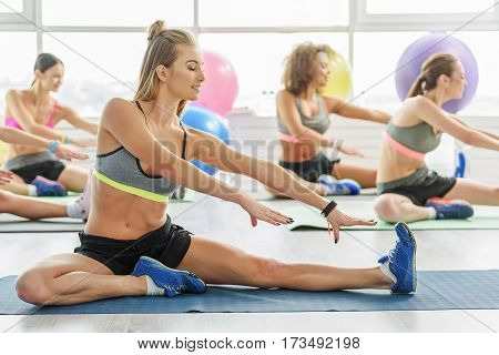 Slim young women are sitting at sports carpets. They are stretching out