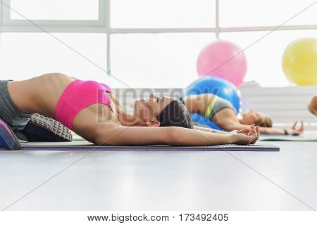 Slim sportive girls are laying on sports mats and doing gymnastic with smile