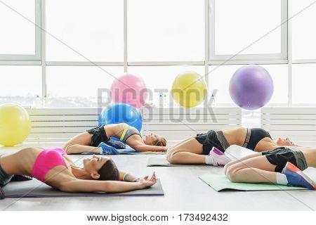 Slim beautiful girl are laying on sports carpets. They are hogging