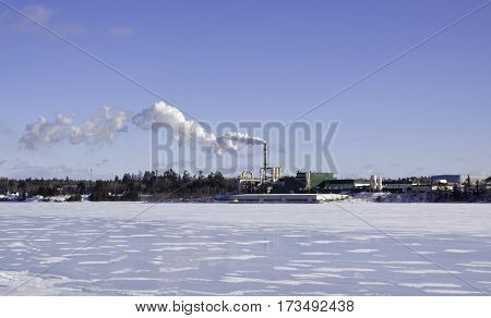 Miramichi, Catham, New Brunswick, February 6, 2017 -- Winter snow scene wide view of large industrial building with smoke stack spewing a cloud of bilious smoke on a bright sunny day in February.