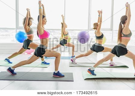 Smiling girls with beautiful figures are doing exercise. They bending one leg at knee and rising hands up