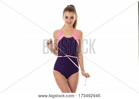young beautiful slender girl stands in the body and keeps on waist Ribbon isolated on white background