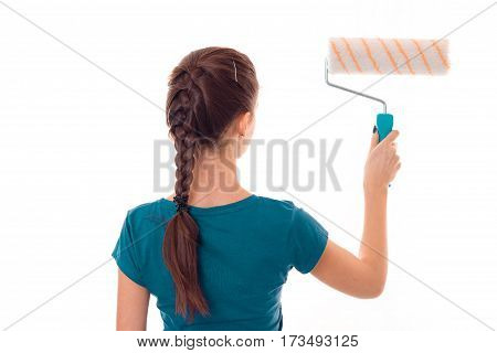 young girl with pigtail worth turning backwards and holding a roller for painting isolated on white background