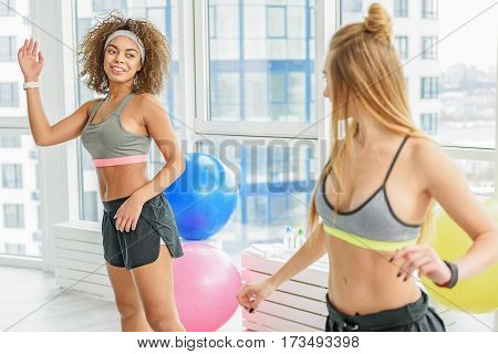 Taut smiling young women are standing near big window. They looking at each other and doing exercise