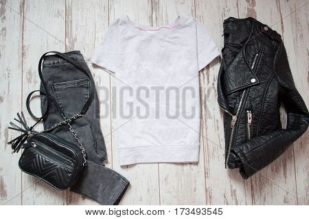 Fashion concept. White T-shirt gray jeans handbag and black leather jacket on a wooden background. top view