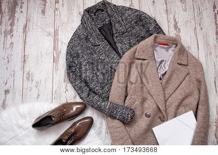 Two woolen coat brown patent leather shoes on a white fur white blank sheet a wooden background. Fashion concept. top view