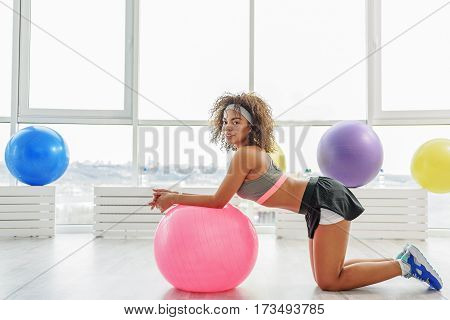 Smiling slim girl is kneeling near pink ball and leaning on it. She looking at camera with interest