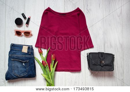 Fashion concept. Maroon top tulips blue jeans black bag sunglasses lipstick. Spring wardrobe. Wooden background. top view