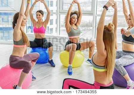 Slim taut girls are sitting on coloured balls and rising hands up. They looking at each other with smile