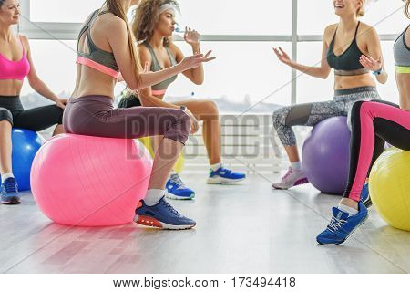 Slim taut young women are sitting in circle on balls and talking with each other