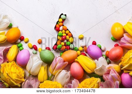 Colorful Easter eggs and spring flowers  on old background. Easter concept with copy space. Flat lay