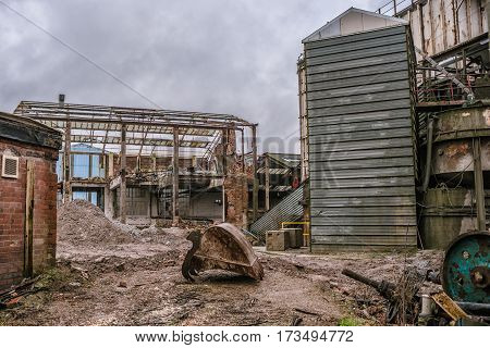 A demolition site of an old factory with rubble and steelwork with a bucket from an excavator  in the foreground and no machinery