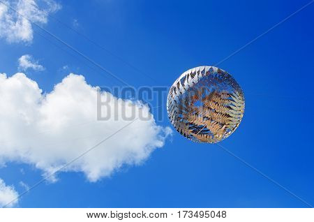 WELLINGTON, NEW ZEALAND - JANUARY 8, 2014: Silver fern-patterned filigreed suspended globe against blue sky with clouds , sculpture by Neil Dawson, Civic Centre, Wellington, New Zealand.