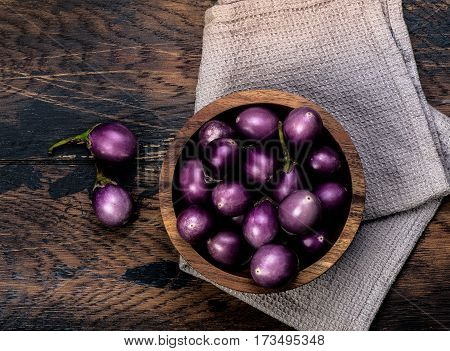 Colorful mini-eggplants on rustic wooden board. Organic raw baby Indian eggplants in a bowl. Top view.