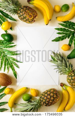 Summer season tropical background with a blank space for a text decorated with various tropical fruits and palm leafs view from above