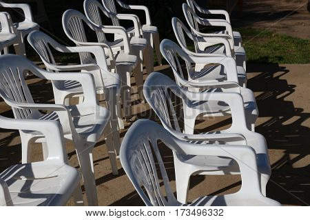 Two rows of white resin patio chairs set up for an event, casting shadows, facing right.