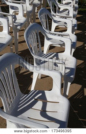 Two rows of white resin patio chairs facing right, set up for an event and casting shadows.