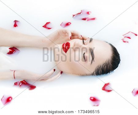 Beautiful Fashion model girl in milk bath, touching face skin, spa and skin care concept. Beauty young Woman with red rose flower relaxing in milk bath. Healthy Face and hands, rejuvenation