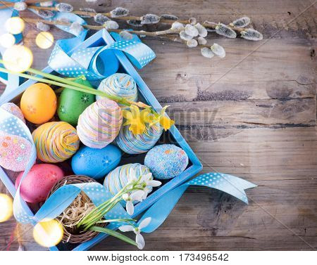 Easter colorful painted eggs on wooden table top background. Beautiful colourful eggs with spring flowers and blue satin ribbon over wood brown backdrop, art border design