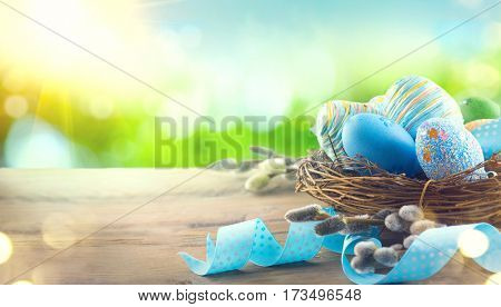 Easter nature spring scene background. Beautiful colorful eggs in nest with flowers on wooden table over spring grass meadow over blue sky with sun. Invitation card border design
