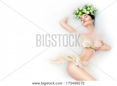 Spa beauty model girl bathing in milk bath, spa and skin care concept. Beauty young Woman with perfect slim body and soft skin, in flower wreath relaxing in milk bath. Rejuvenation poster