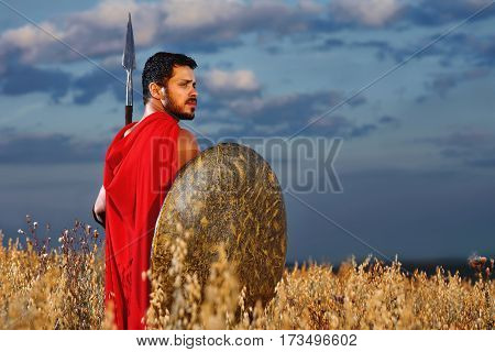 Ready for combat. Confident male Greek or Roman warrior in a red cape looking away thoughtfully standing in the field with a spear and a shield copyspace confidence masculinity guardian concept