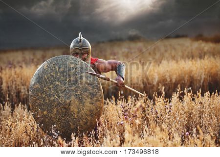 Attack Shot of an armored Roman legionary warrior covering himself with a shield ready to attack his enemy with a spear on the battlefield copyspace war fight bravery hero concept.