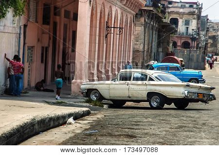 Havana, Cuba, July, 11, 2006. - Looking over street in old Havana, vintage cars parked and some locals on the streets