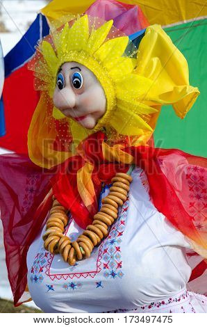 Shrovetide doll in embroidered white shirt and bright shawls with bunch of bagels on neck
