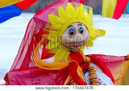 Pancake doll in bright multi-colored dress with bunch of bagels on neck