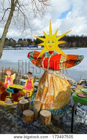 Shrovetide doll in bright multi-colored dress with face-sun on background of spring landscape