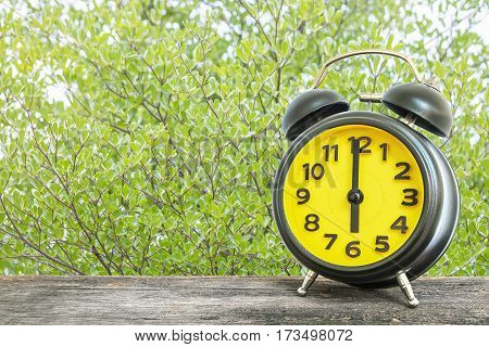 Closeup black and yellow alarm clock for decorate in 6 o'clock on old brown wood desk on green leaves in the park textured background
