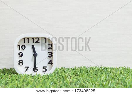 Closeup white clock for decorate show a half past eleven or 11:30 a.m. on green artificial grass floor and cream wallpaper textured background with copy space