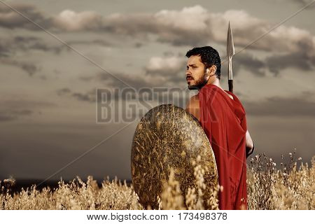Fighter in soul. Sepia toned shot of brave young male ancient Greek or Roman warrior looking away thoughtfully standing alone on the battlefield copyspace thinking historical personality hero concept