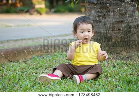 Closeup cute asian kid pick up hay into his mouth on grass floor in the park background