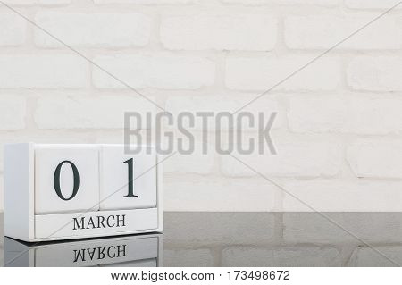 Closeup white wooden calendar with black 1 march word on black glass table and white brick wall textured background with copy space selective focus at the calendar