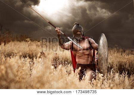 Art of war. Sepia toned shot of a Roman legionary warrior throwing his spear on the battlefield dramatic gloomy sky on the background copyspace power attack war fighter armor helmet culture concept