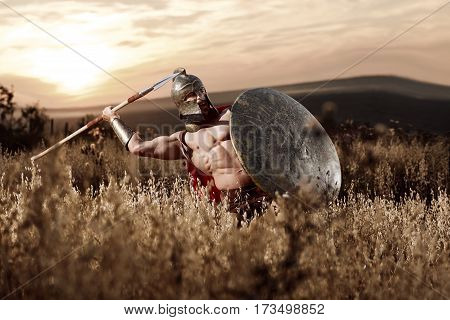 War god. Sepia toned shot of a muscular strong Roman legionary warrior with perfectly shaped athletic body throwing his spear during the battle in the field on dusk power fearless war concept